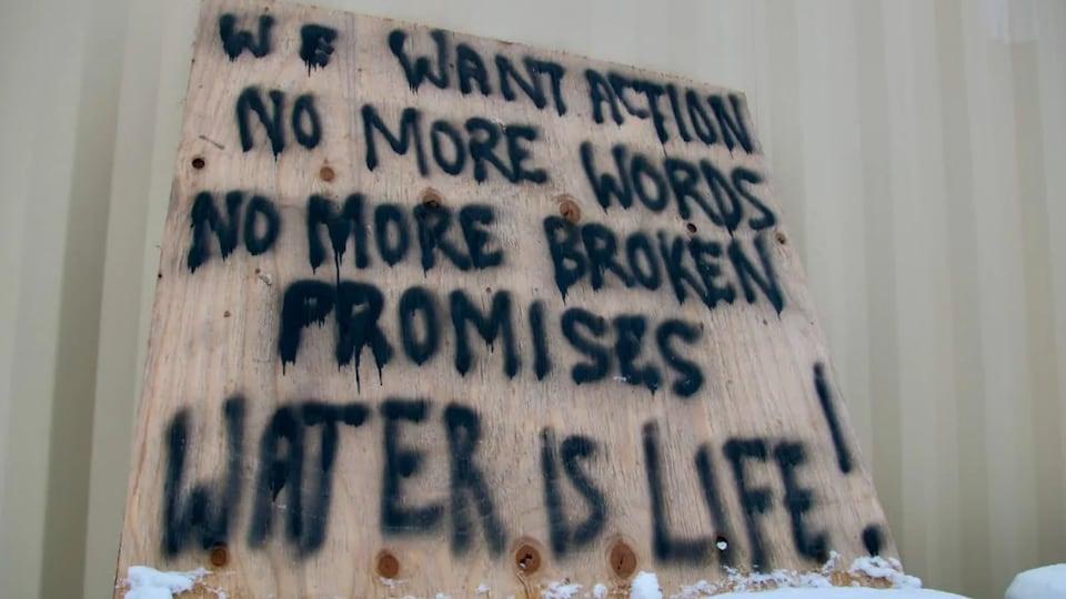 Une affiche dans la communauté de Neskantaga sur laquelle on peut lire : « Nous voulons des actes. Les mots, ça suffit. Plus de promesses rompues. L'eau c'est la vie ».
