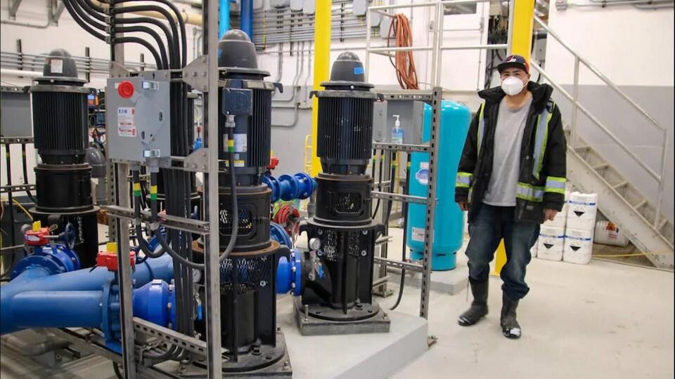 Un opérateur près de pompes à eaux.