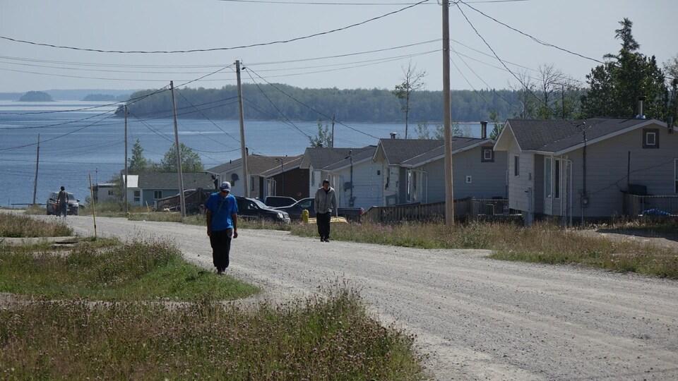 Au premier plan, deux personnes qui marchent sur la route, avec le lac à l'arrière.