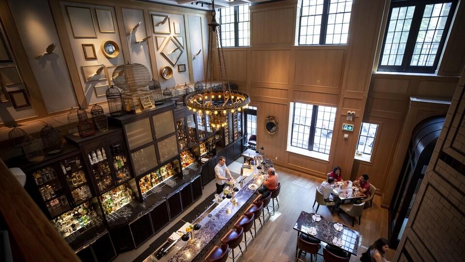 Une grande salle de restaurant avec un bar, de tables et des chaises.