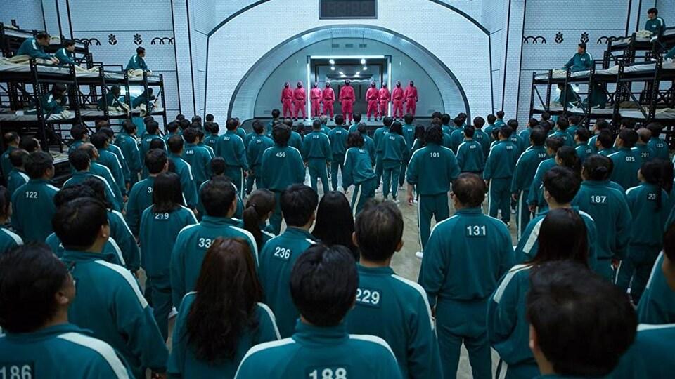 Des dizaines de personnes vêtues de combinaisons vertes regardent d'autres personnes masquées vêtues de combinaisons rouges qui sont sur un piédestal.