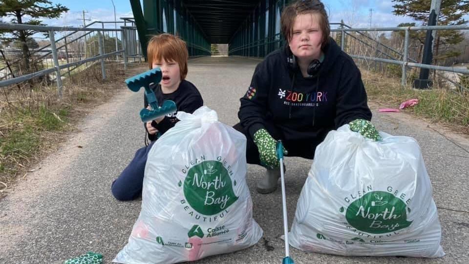 Deux jeunes tenant de longues pinces montrent leurs sacs d'ordures bien remplis.