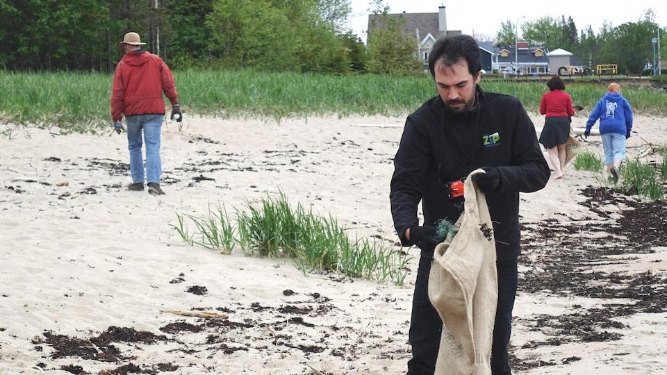 Des canettes vides et divers objets laissés sur la plage sont ramassés.