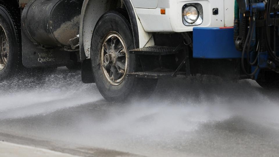 Un camion nettoie à grande eau une rue.