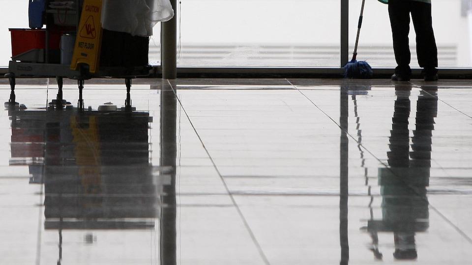 Un homme nettoie le plancher avec une vadrouille.