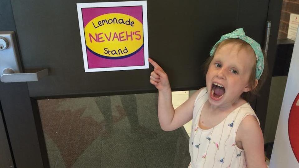 Nevaeh Denine montre du doigt une affichette qui annonce son comptoir de limonade.