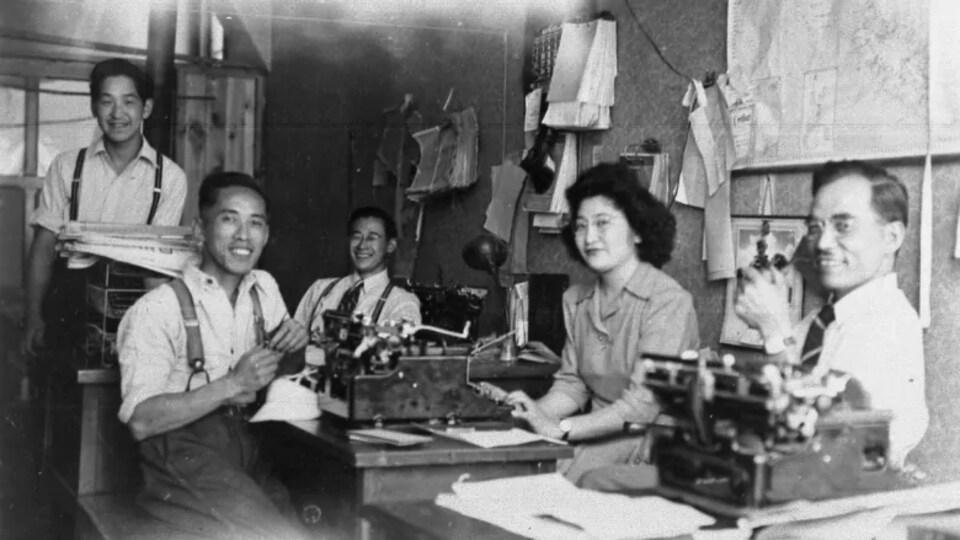 Un groupe d'employés du journal dans une salle de presse.