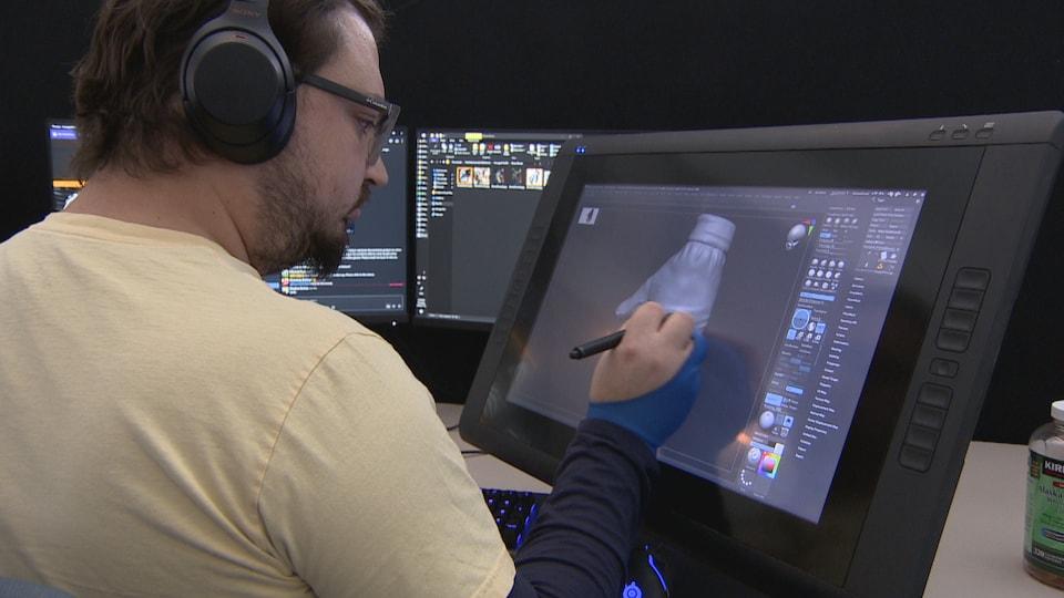 Un homme dessine une main sur un écran tactile.