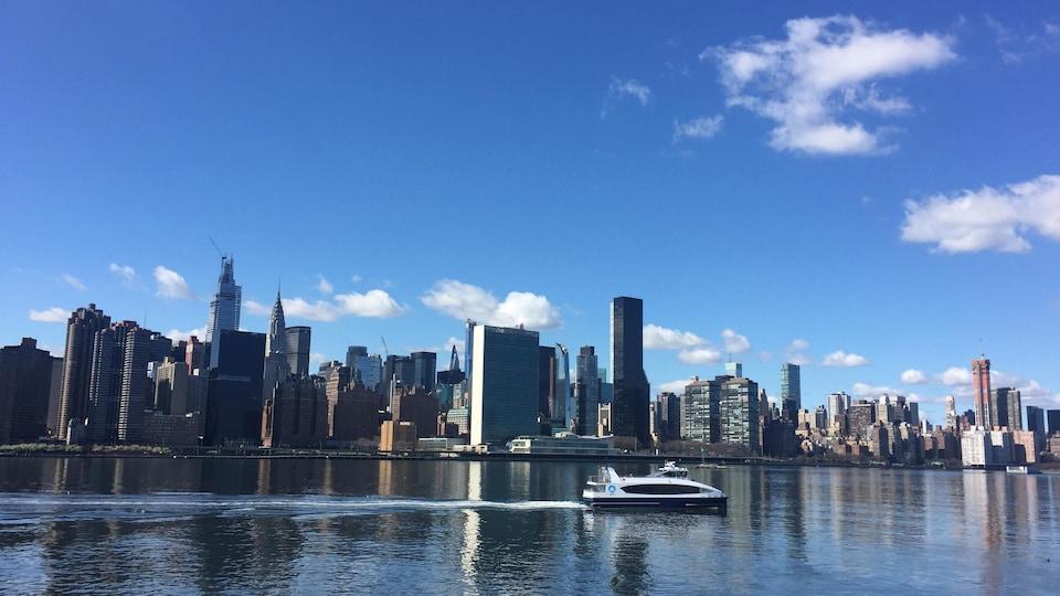 Un petit bateau circule devant la silhouette des gratte-ciel de New York.
