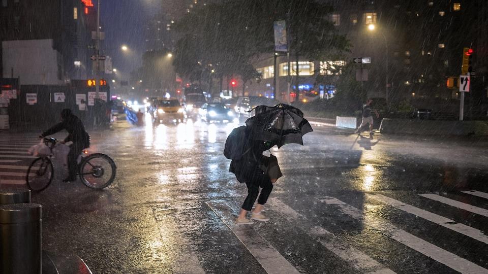 Une femme sous son parapluie traverse une rue de New York alors qu'un torrent de pluie s'abat sur la ville.
