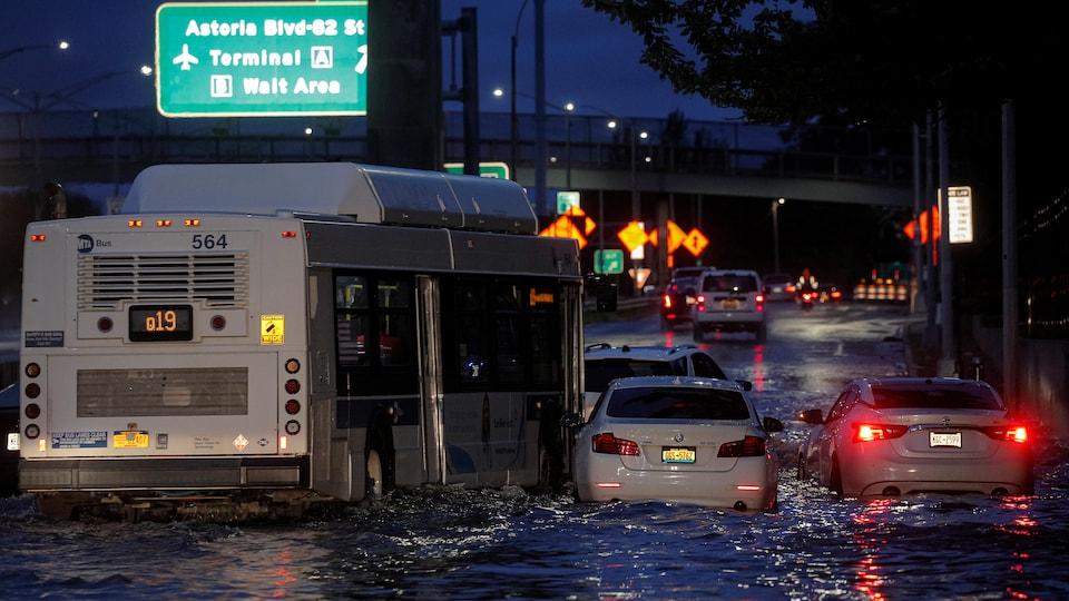 Queens, New York'ta bir otobüs sular altında kalan bir otoyolda terk edilmiş arabaların yanından geçiyor.