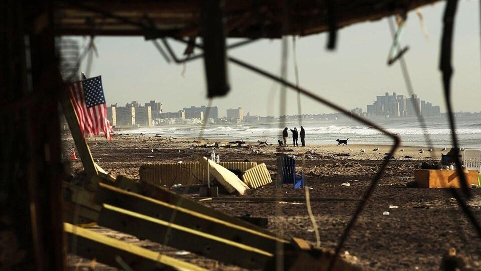 Des infrastructures brisées et un drapeau américain déchiré se trouvent le long d'une plage jonchées de déchets.