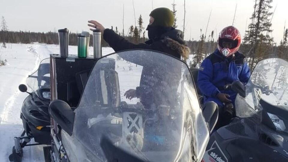 Jean Marc Ngosso portant un casque est assis sur une motoneige pendant qu'un homme avec une cagoule se tient debout devant sa motoneige.