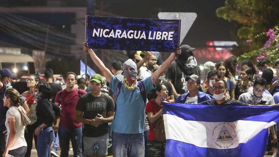 Un homme se tient devant des manifestants avec une affiche où on peut lire «Nicaragua Libre»