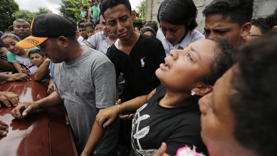 Une famille pleure au-dessus d'un cercueil.