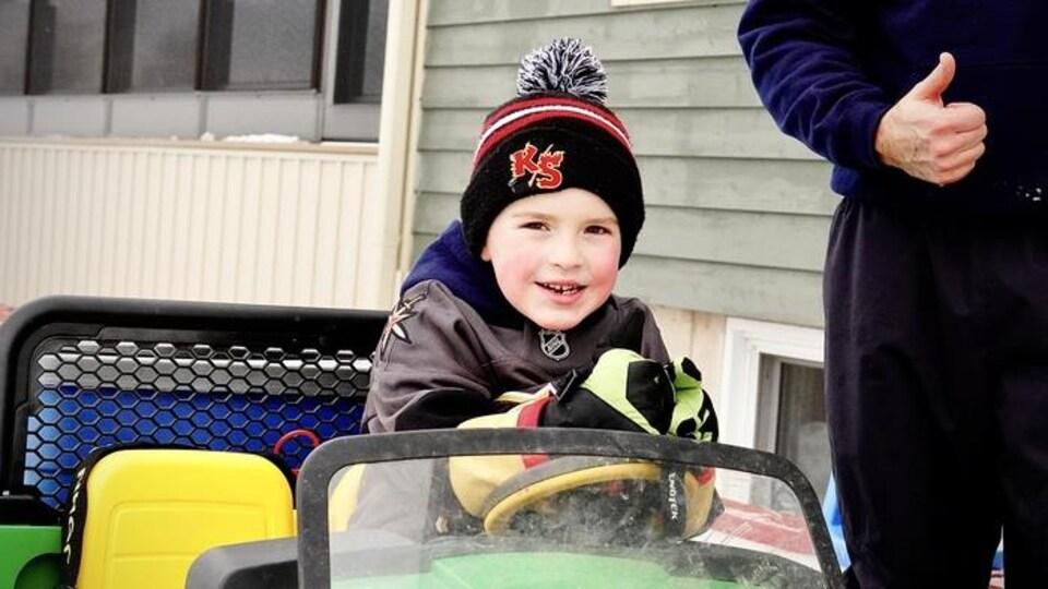 Un petit garçon à bord d'un bolide extérieur.