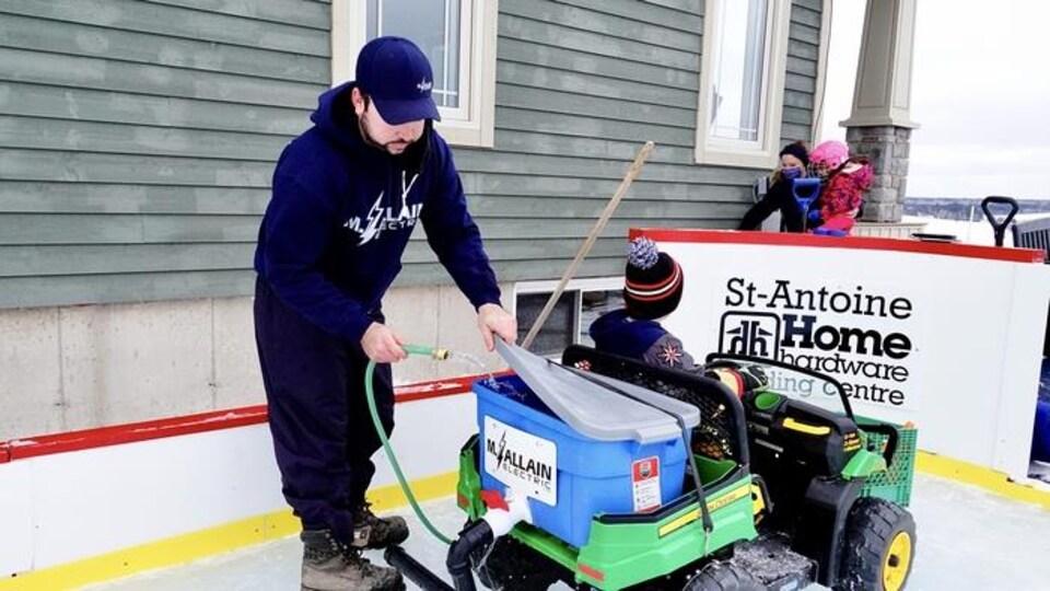 Une patinoire extérieure. Un petit garçon est à bord d'une minisurfaceuse, et son père met de l'eau dans un seau à l'aide d'un tuyau pour pouvoir ensuite polir la glace. En arrière-plan, une dame tient dans ses bras une petite fille avec un casque de hockey rose sur la tête.