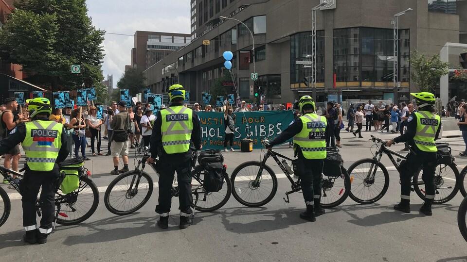 Des policiers sont debout derrière leur vélo et bloquent la rue où se trouvent les participants.