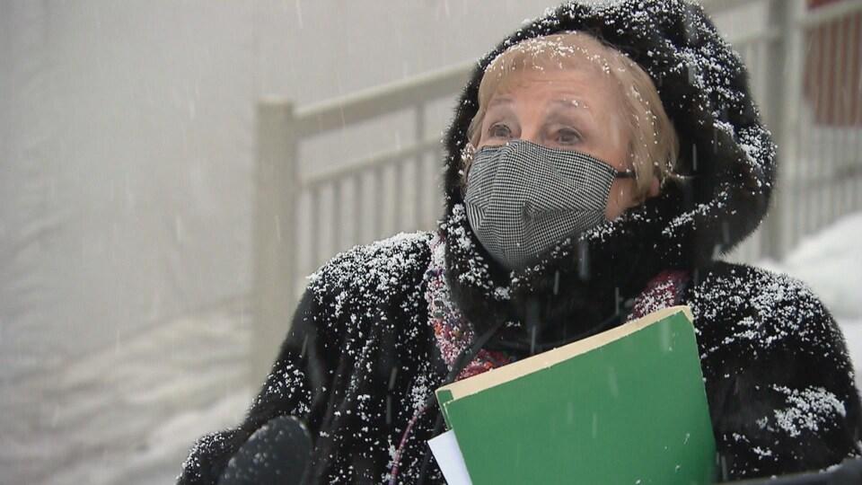 Nicholle Gervais à l'extérieur en hiver avec des documents dans les mains.
