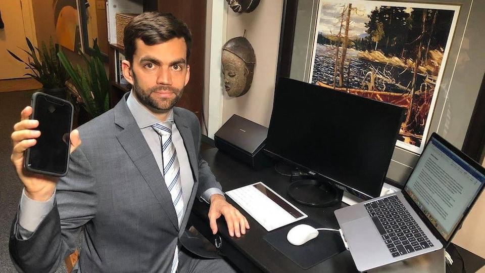 L'avocat Nick Wright, assis à son bureau, montre un téléphone cellulaire à la caméra.
