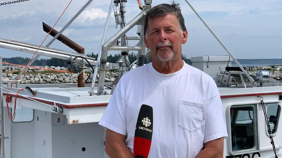 Jamey Nickerson interviewé sur un quai, devant un bateau.