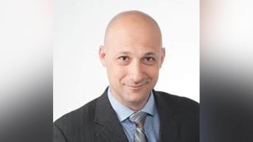 Photo de M. Salomone, un homme chauve, qui porte un veston gris.