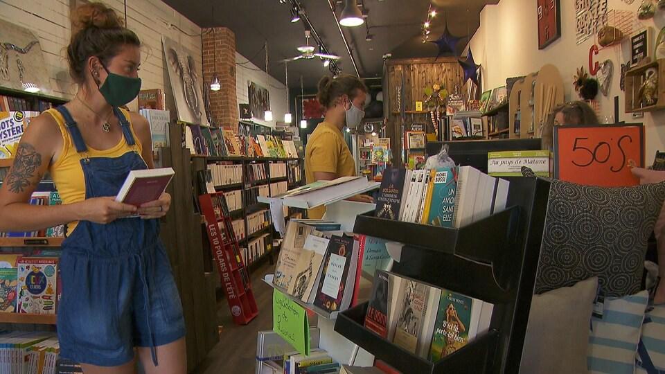 Une jeune femme et un jeune homme dans les rayons de la Chouette librairie.