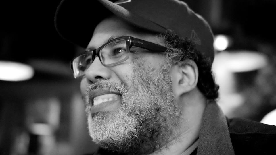 Photo en noir et plan de Nicolas Boivin. L'homme porte la barbe ainsi que des lunettes et une casquette. Il sourit sur la photo.