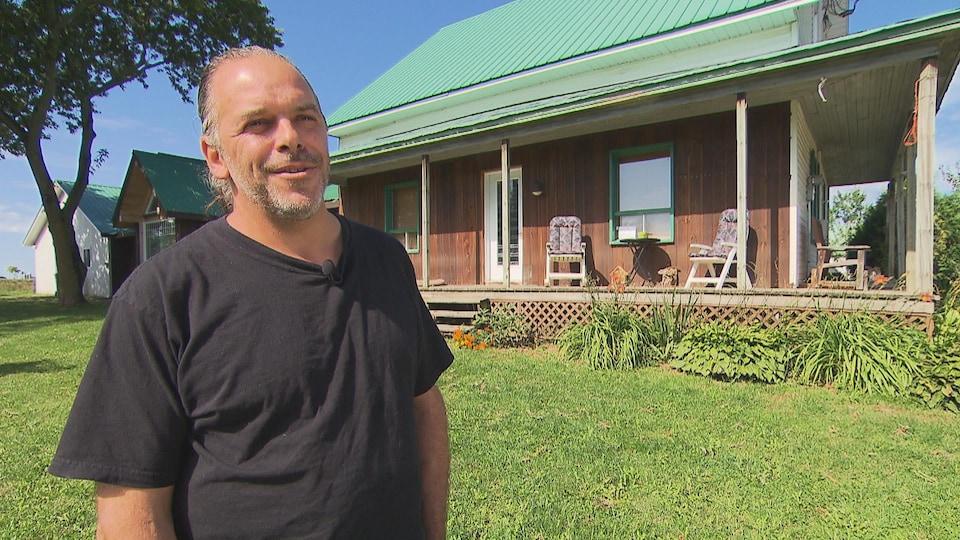 Un homme devant une maison en entrevue à la caméra.