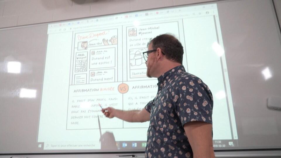 Un enseignant pointe un tableau blanc.