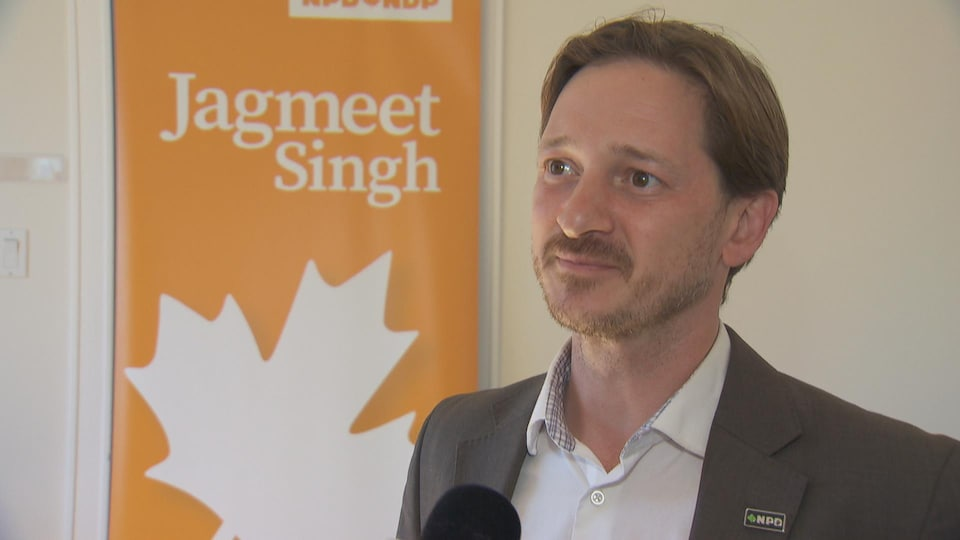 Nicolas Thibodeau en entrevue devant une affiche de son parti.