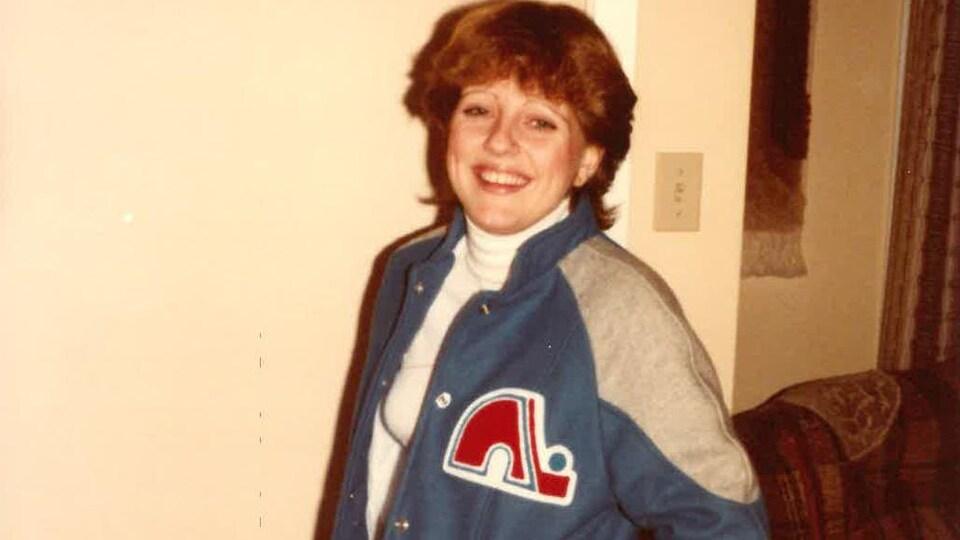 Une jeune Nicole Bouchard pose dans une veste des Nordiques