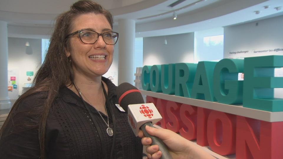 Une femme répond à une question non loin de la reproduction des mots courage en turquoise et passion en rouge.