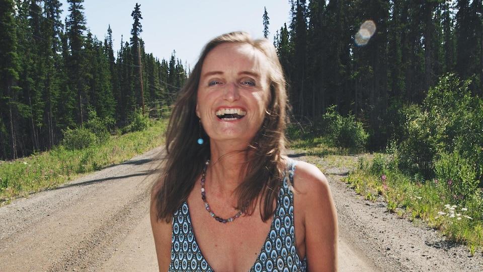 Nicole Edwards sourit dans la forêt.