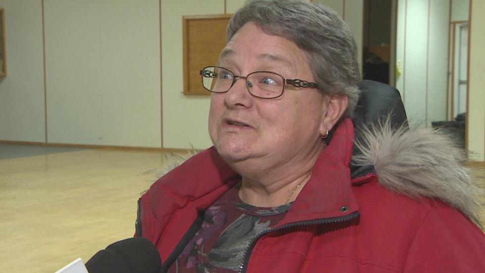 Gros plan sur le visage de Nicole Fister, qui répond aux questions du journaliste.