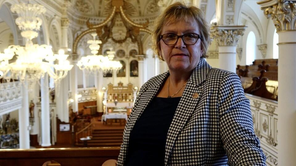 Nicole Lavoie fait face à la caméra, elle est à l'intérieur de l'église Sainte-Cécile du Bic.