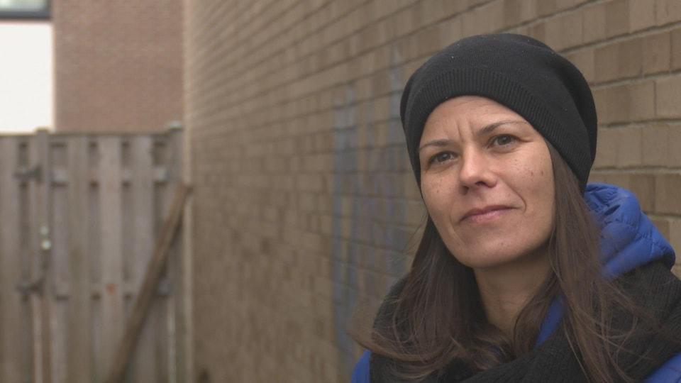 Nicole Lavoie est dans une ruelle et porte un manteau d'hiver et une tuque noire.