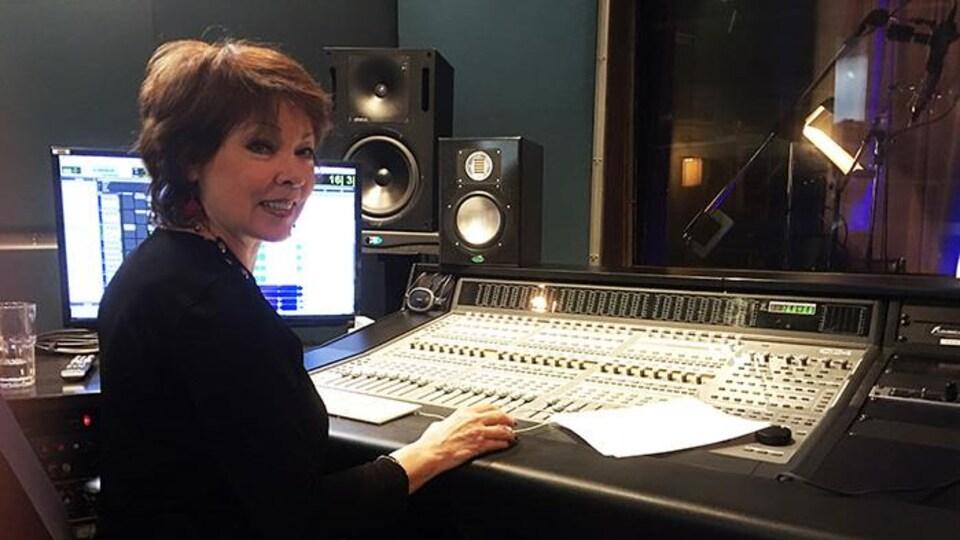 Nicole Martin est devant une console de son, dans un studio.