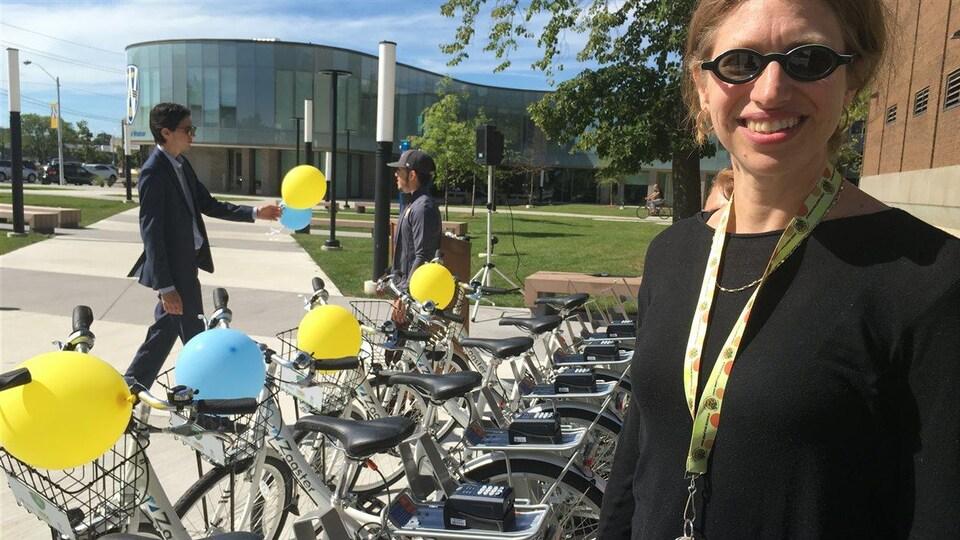 Une femme est photographiée devant des vélos.