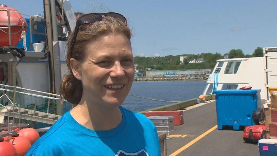Elle est en entrevue sur un quai devant le bateau des scientifiques.