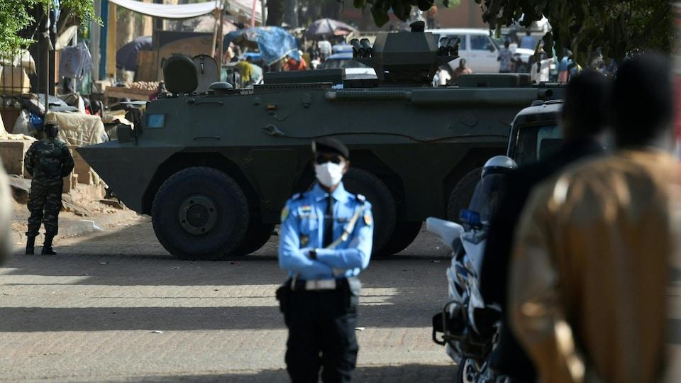 Le véhicule est placé en travers de la rue, entouré de soldats.