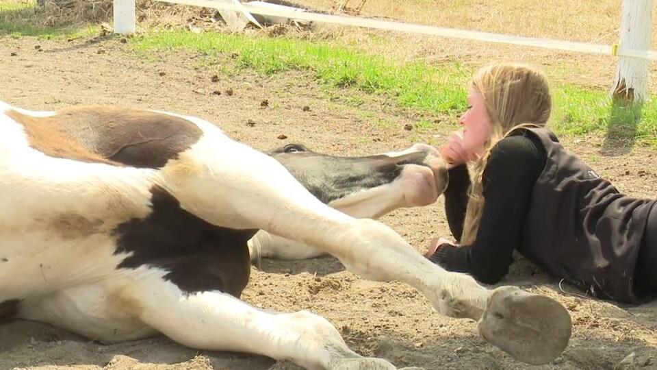 Un cheval et une jeune femme sont couchés au sol et jouent ensemble.