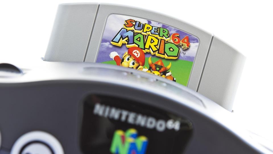 Une photo d'une console de jeux vidéo Nintendo 64 dans laquelle est insérée une cartouche du jeu Super Mario 64.