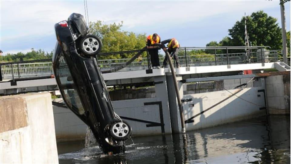 Une voiture est en train d'être sortie d'un canal.
