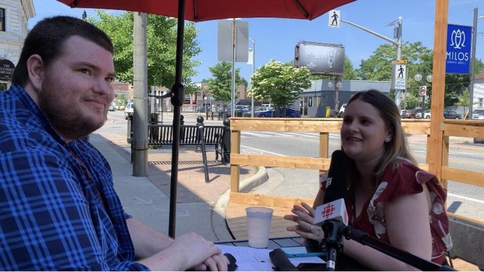 Un jeune couple est assis à la terrasse d'un restaurant.