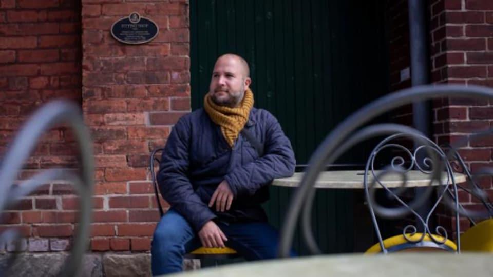 Un homme est assis sur une terrasse.