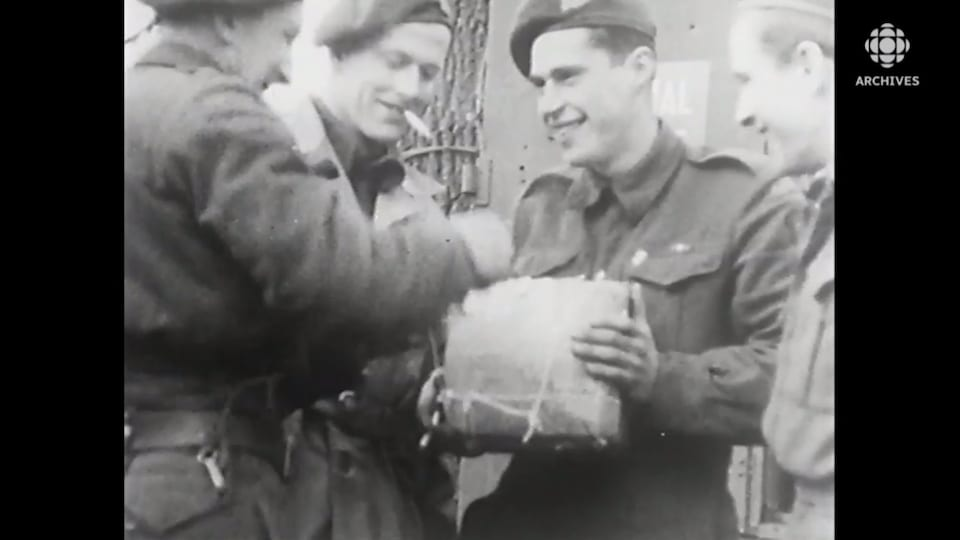 Des soldats souriants ouvrent un cadeau de Noël.