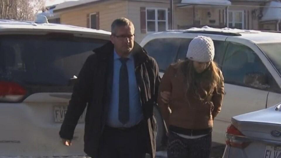 Noémie Morin, escortée par un policier, lors de son arrivée au palais de justice de Trois-Rivières.