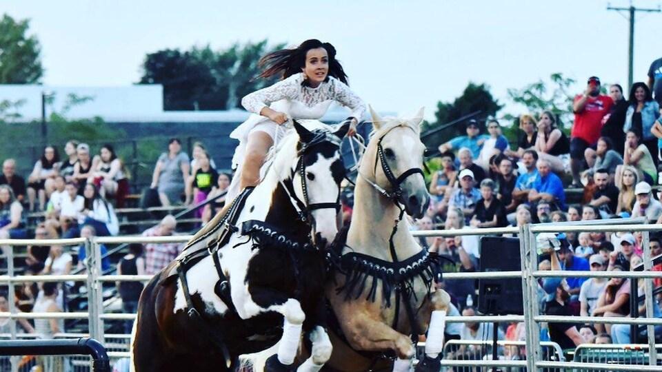 Une femme est debout sur deux chevaux qui sautent un obstacle.