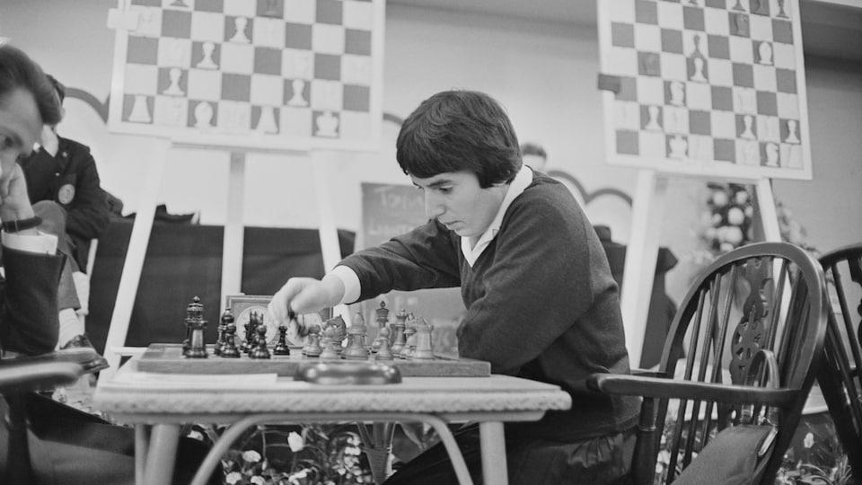 Dans une photo en noir et blanc, la femme est assise devant un jeu d'échecs face à un adversaire.